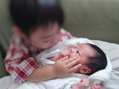 赤ちゃんを抱っこする3歳児