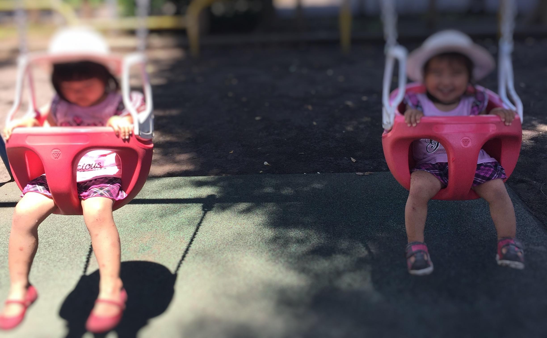 バケットシートブランコに赤ちゃんと子供が乗っているところ