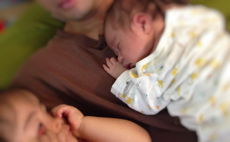 パパとお腹を密着させて寝る新生児