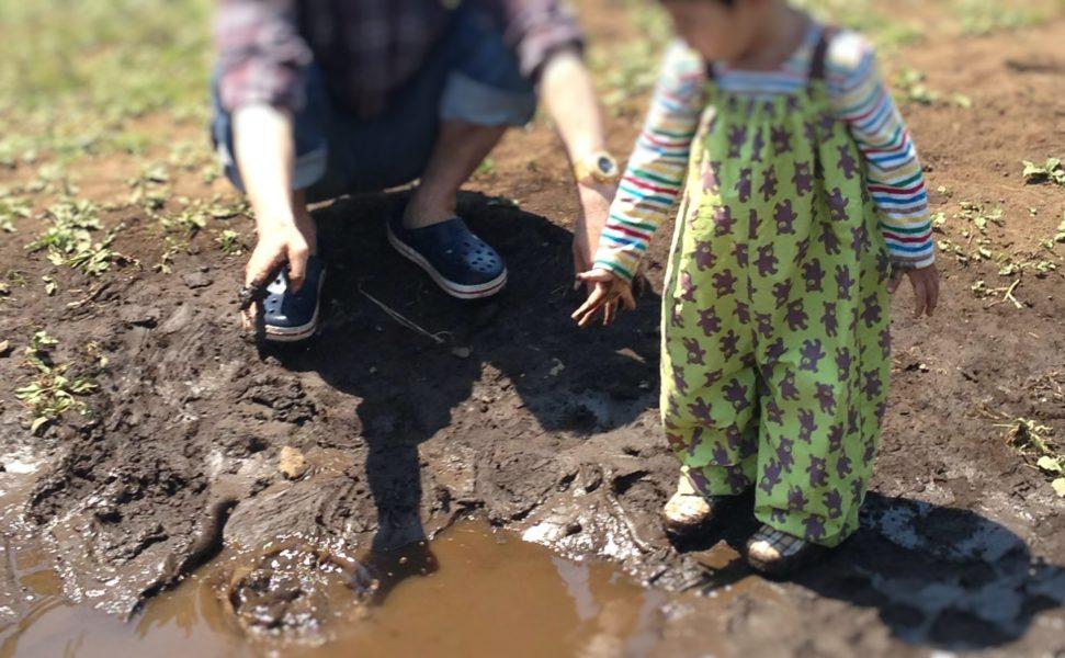 幼児がプレーパークでエプロンをかけて泥遊びをしているところ