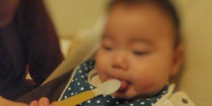赤ちゃんが初めての離乳食をスプーンで食べているところ