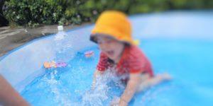幼児が熱中症対策の帽子をかぶって水遊びをしている様子