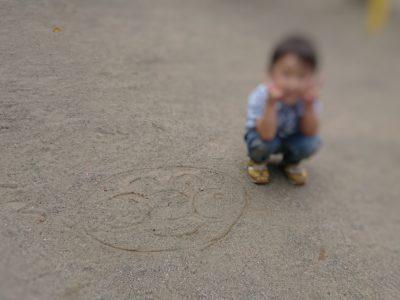 外遊びで砂にお絵かきをしている