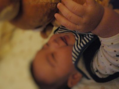 4ヶ月の赤ちゃんがおもちゃの人形で遊んでるところ